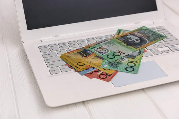 Banknoty dolara australijskiego na białej klawiaturze laptopa