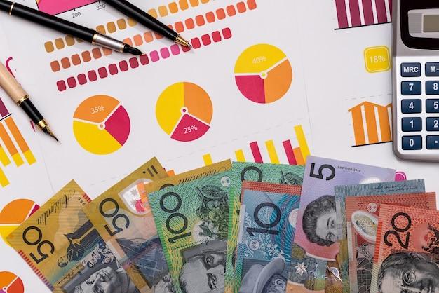 Banknoty dolara australijskiego na wykresach biznesowych z kalkulatorem i piórem