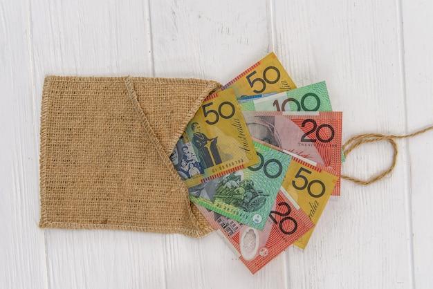 Banknoty dolara australijskiego z materiałową kopertą na jasnym tle