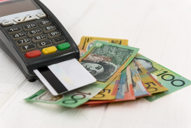 Banknoty dolara australijskiego z terminalem i kartą kredytową