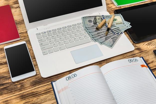 Banknoty dolara na klawiaturze komputera i pusty notatnik