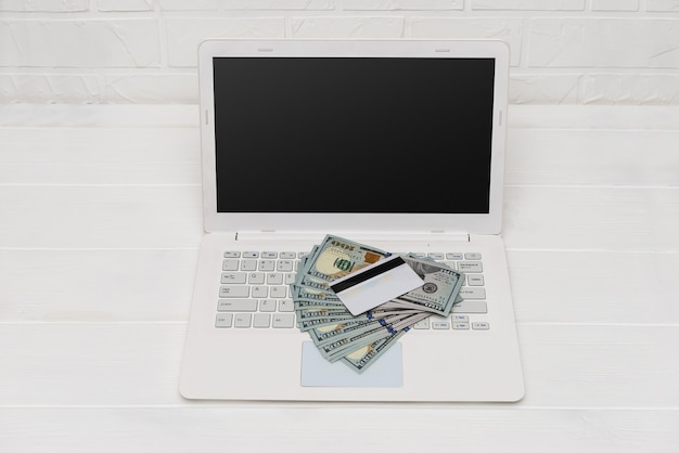 Banknoty dolara na klawiaturze laptopa i karcie kredytowej