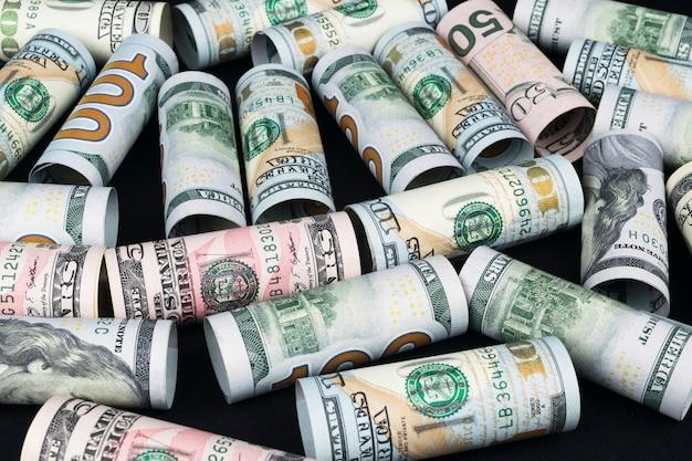 Banknoty dolara toczą się w innych pozycjach. amerykańska waluta amerykańska na czarnej tablicy. banknoty dolarowe w rolkach we wszystkich nominałach