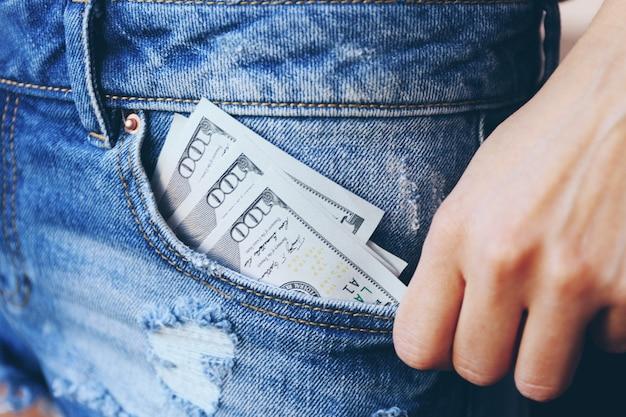 Banknoty dolara w zbliżenie kieszeni dżinsów
