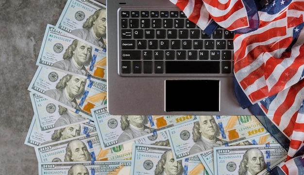 Banknoty dolarów amerykańskich umieszczone na klawiaturze komputera widok z góry flagi amerykańskiej