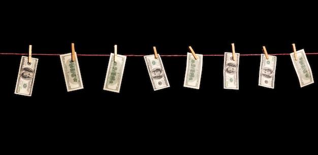 Banknoty dolarów wiszą na linie odizolowanej na czarno