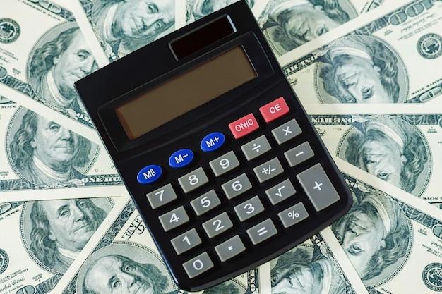 Banknoty dolarowe i kalkulator w środku. koncepcja finansów i rachunkowości.