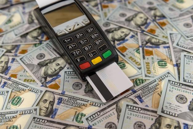 Banknoty dolarowe i terminal z kartą kredytową