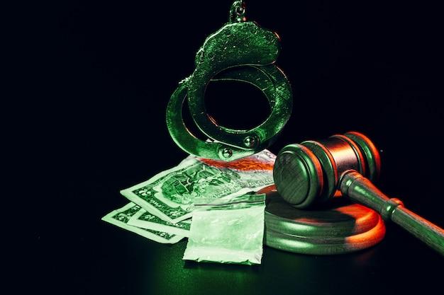 Banknoty dolarowe, kajdanki i młotek na czarny stół