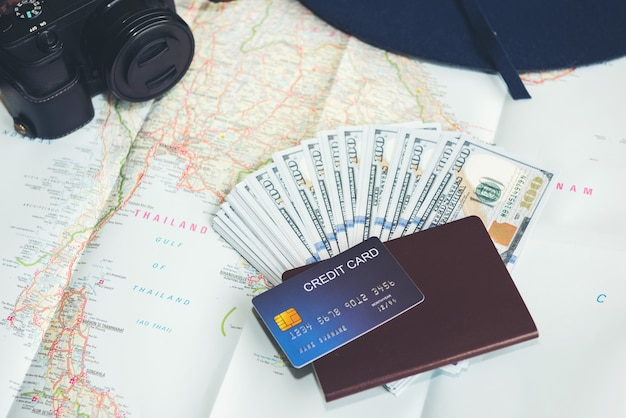 Banknoty dolarowe, karta kredytowa, paszport, aparat fotograficzny i niebieski kapelusz