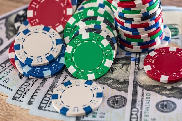 Banknoty dolarowe na drewnianym stole z żetonami w kasynie