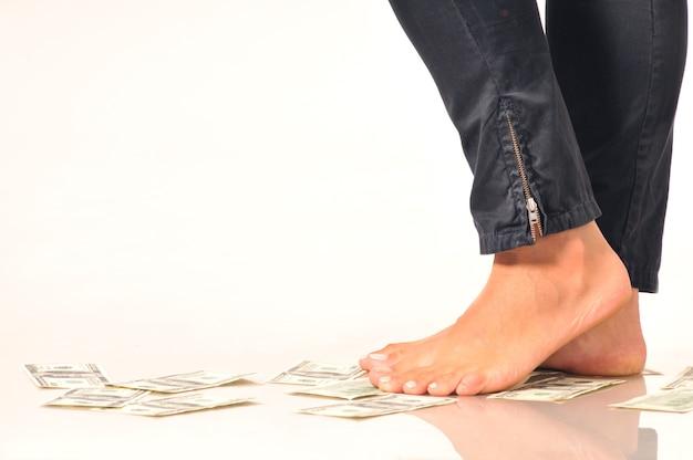 Banknoty dolarowe na podłodze pod nogami kobiety sugerują spadek lub dewaluację walut banknotów dolarowych