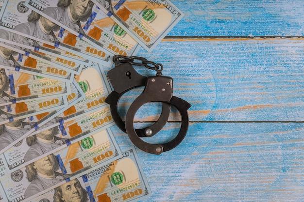Banknoty dolarowe pieniądze korupcja gotówkowa, brudne pieniądze przestępstwa finansowe metalowych kajdanek policyjnych
