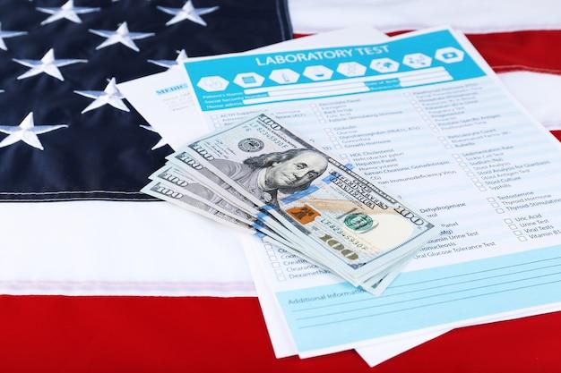 Banknoty dolarowe w formie testu laboratoryjnego na amerykańskiej fladze