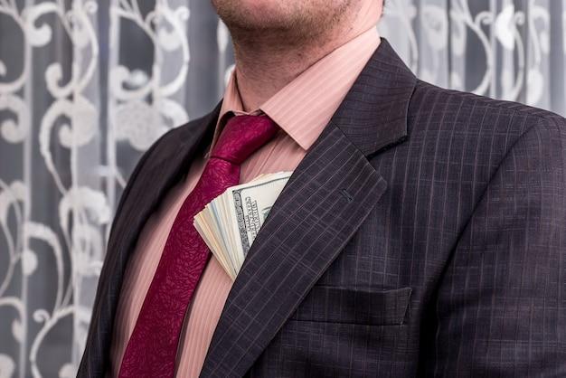 Banknoty dolarowe w kieszeni marynarki biznesmena, z bliska