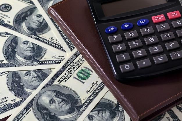 Banknoty dolarowe, zamknięty notatnik i kalkulator. koncepcja finansów, rachunkowości lub oszczędzania.
