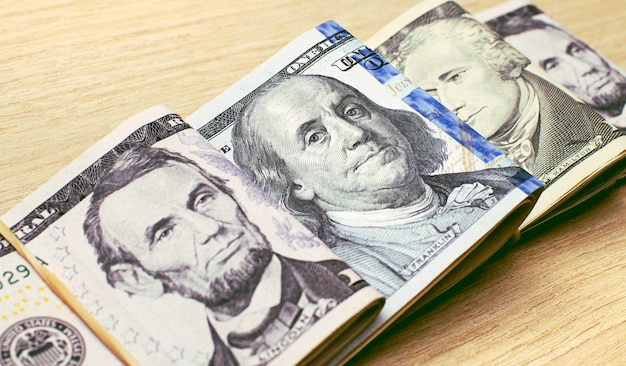Banknoty dolarowe złożone na drewnianym stole w fotografii zbliżeniowej