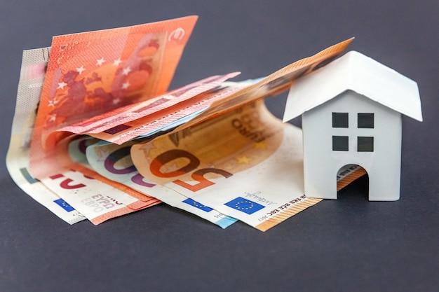 Banknoty euro i symboliczny mały domek z zabawkami