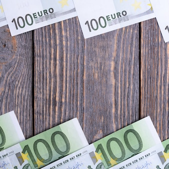 Banknoty euro leżą w ramie w drewnianej przestrzeni.