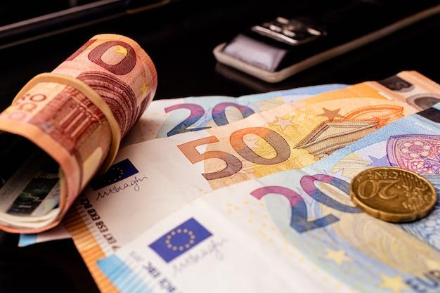 Banknoty euro na biurku z rolką pieniędzy i czarnym zszywaczem