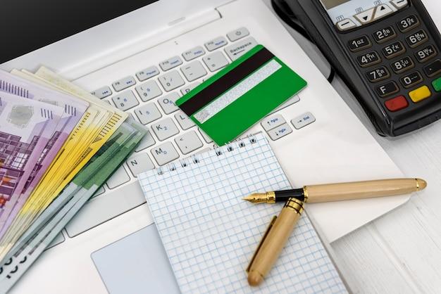 Banknoty euro na laptopie i terminalu bankowym