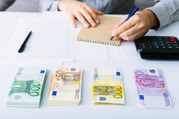 Banknoty euro są ułożone w stos. człowiek robi swoją księgowość. podział wydatków w małej firmie. oszczędności, depozyty, pożyczki i oprocentowanie.