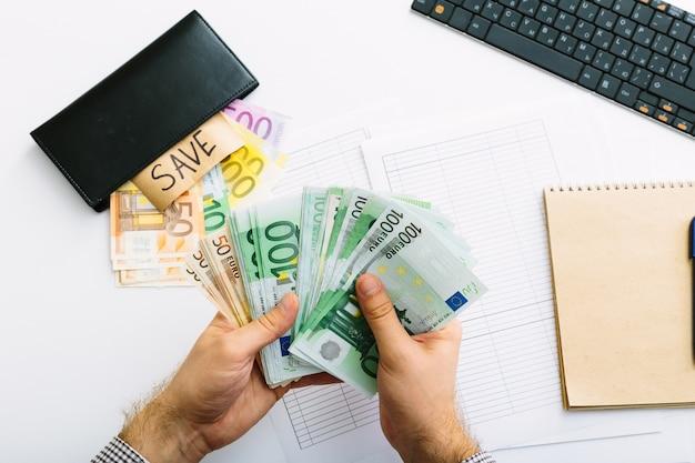 Banknoty euro są ułożone w stosy. mężczyzna robi swoją księgowość. podział wydatków w małej firmie.
