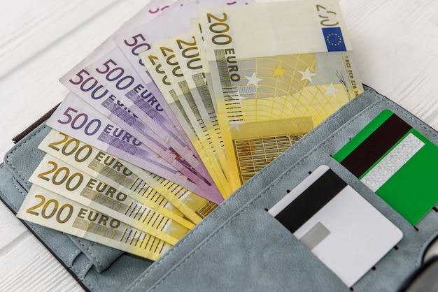 Banknoty euro z kartą kredytową w portfelu