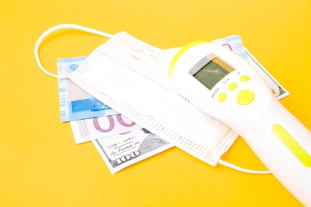 Banknoty i bezdotykowa maska na twarz z termometrem, żółte tło