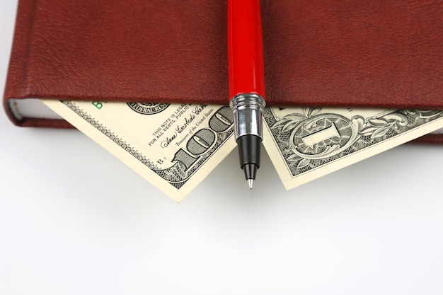 Banknoty i czerwony długopis leżące wewnątrz notesu