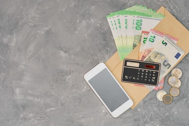 Banknoty i monety euro, komunikator, kalkulator i długopis z notatnikiem, koncepcja biznesu, finansów, płatności podatków. rachunkowość wydatków rodzinnych. widok z góry, kopia przestrzeń, szare tło vintage