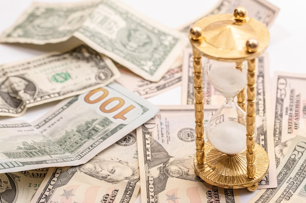 Banknoty klepsydry i dolara amerykańskiego. pojęcie inwestycji lub inflacji.