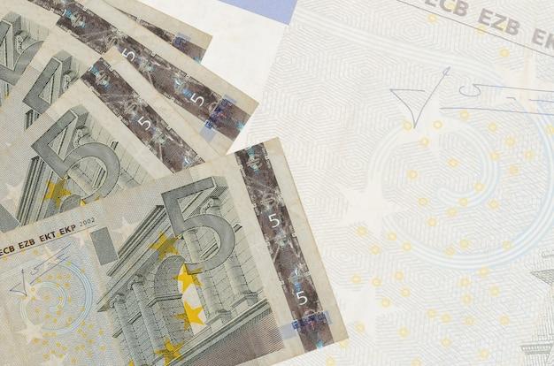 Banknoty o nominale 5 euro leżą w stosie na ścianie dużego półprzezroczystego banknotu. streszczenie ściany biznesu z miejsca na kopię
