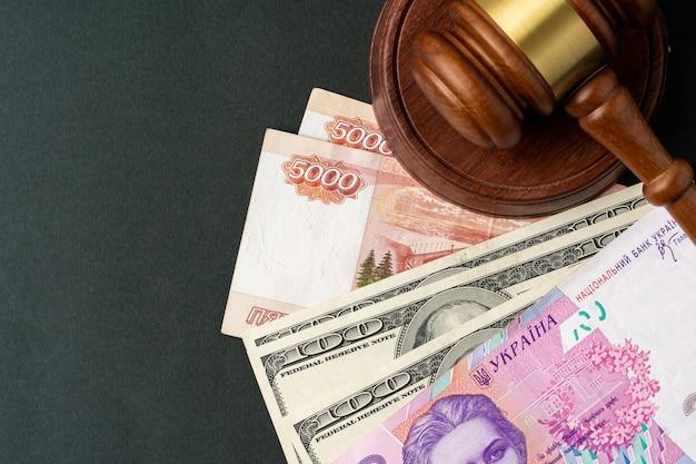 Banknoty pieniądze z młotek sędziego. koncepcja korupcji z walutą rubli rosyjskich, hrywny ukraińskiej i dolarów amerykańskich