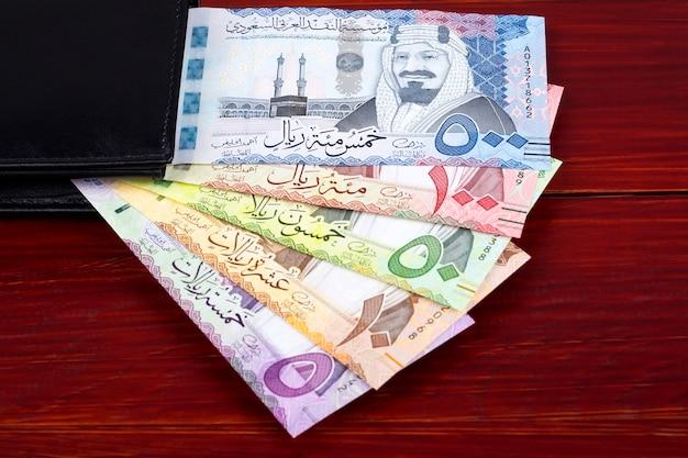 Banknoty riyal saudyjskie w czarnym portfelu