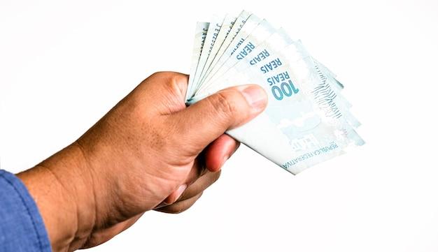 Banknoty sto reali z brazylii, dzień wypłaty zasiłku socjalnego. 100 reali dostarczonych męską ręką, nadzwyczajna pomoc od rządu.