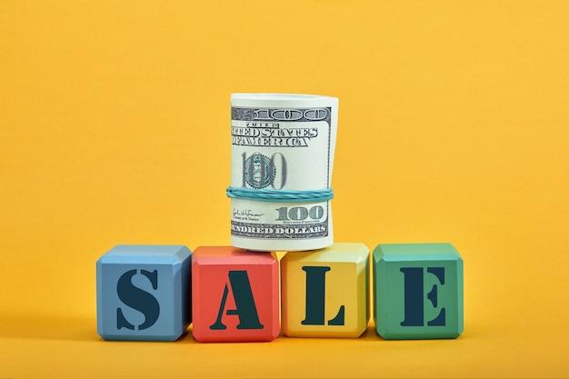 Banknoty toczą się na różnych kolorowych blokach ze słowem sprzedaż na białym tle na żółtej ścianie