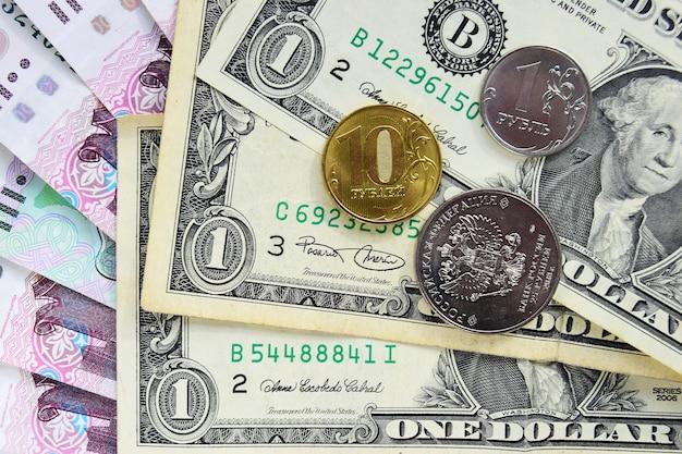 Banknoty w dolarach amerykańskich są umieszczane na rosyjskich rublach papierowych, na których znajdują się monety. kryzys finansowy i wybór waluty na oszczędności, pojęcie dewaluacji rubla.