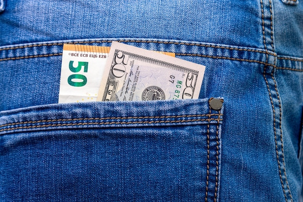 Banknoty w nominałach 50 euro i dolarów w zbliżeniu tylnej kieszeni niebieskich dżinsów.