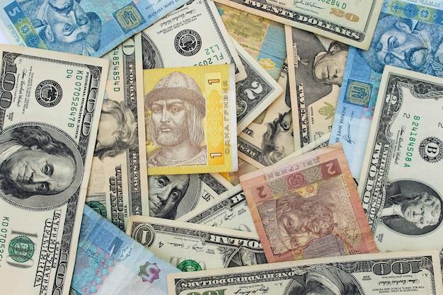 Banknoty w tle: dolary amerykańskie i hrywny ukraińskie
