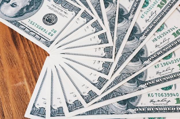 Banknoty w wysokości stu dolarów rozkładają się jak wachlarz na drewnianych deskach.