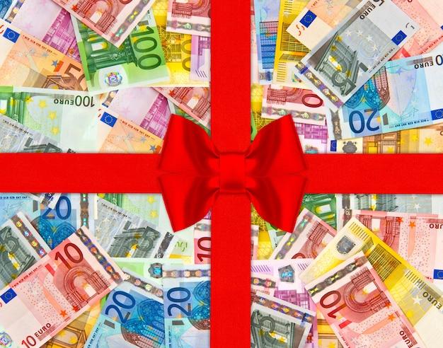 Banknoty waluty euro z czerwoną wstążką prezent i łuk. europejskie pieniądze tło