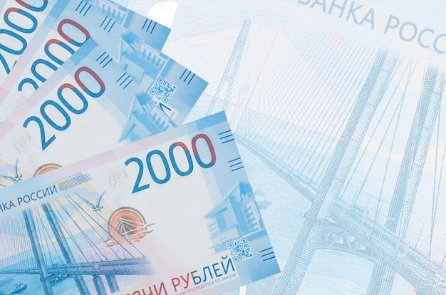 Banknoty za 2000 rubli rosyjskich leżą w stosie na ścianie dużego półprzezroczystego banknotu.
