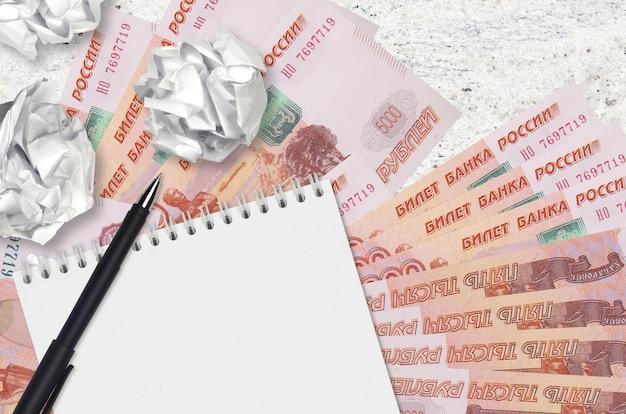 Banknoty za 5000 rubli rosyjskich i kulki zmiętego papieru z pustym notatnikiem. złe pomysły lub mniej pomysłów na inspirację. poszukiwanie pomysłów na inwestycje
