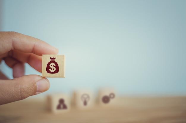 Bankowość i finanse, koncepcja planowania finansowego: ręka wybiera drewniane kostki z ikonami torebek dolara amerykańskiego. zarządzanie pieniędzmi korporacyjnymi aby zachować spójność z dochodami w każdym kwartale.