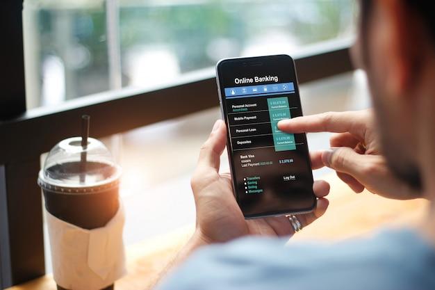 Bankowość mobilna. człowiek za pomocą technologii bankowości internetowej na urządzeniu z ekranem dotykowym.