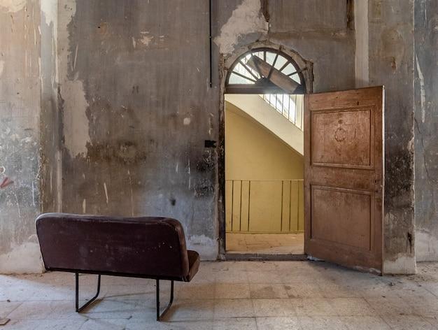 Bankrutująca kanapa przed zabytkowymi drzwiami
