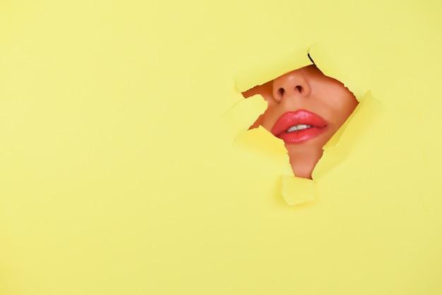 Banner reklamowy salon kosmetyczny z miejsca na kopię. widok jaskrawe wargi z błyskotliwością przez dziury w żółtym papierowym tle.