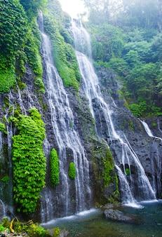 Banyumala twin wodospad na zboczu góry na bali. kaskada wodospadu w dżungli w tropikalnym lesie deszczowym ze skałą i turkusowym błękitnym stawem.