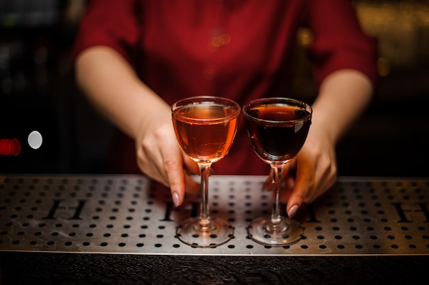 Baran kobieta trzyma dwa eleganckie szklanki z koktajlami